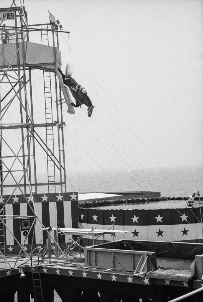 A rider and horse leap from a platform into a pool of water as part of a boardwalk show, Atlantic City, New Jersey, 1969. (Photo by Tim Boxer/Getty Images)